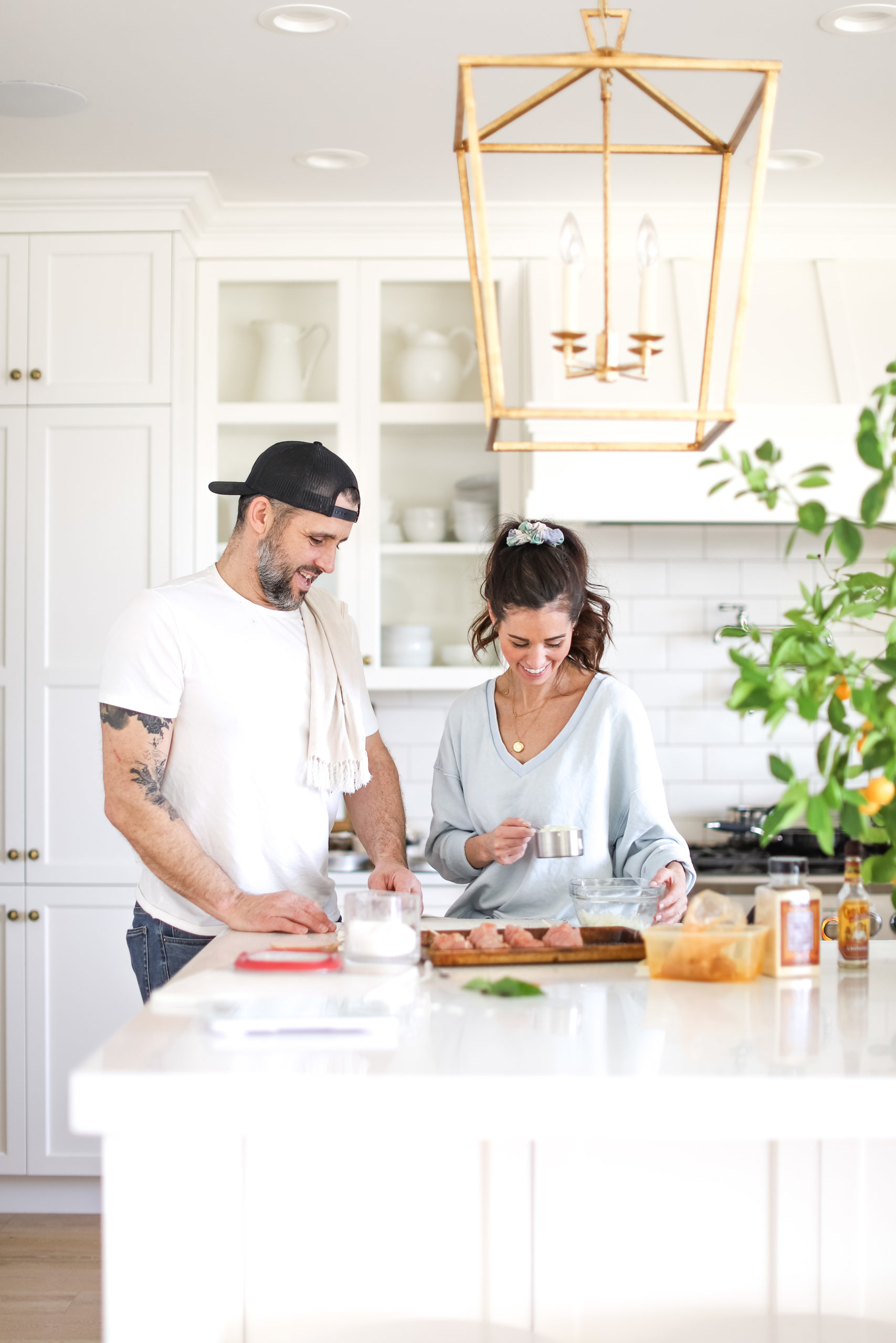 husband and wife cooking homemade chicken parmesan in kitchen together