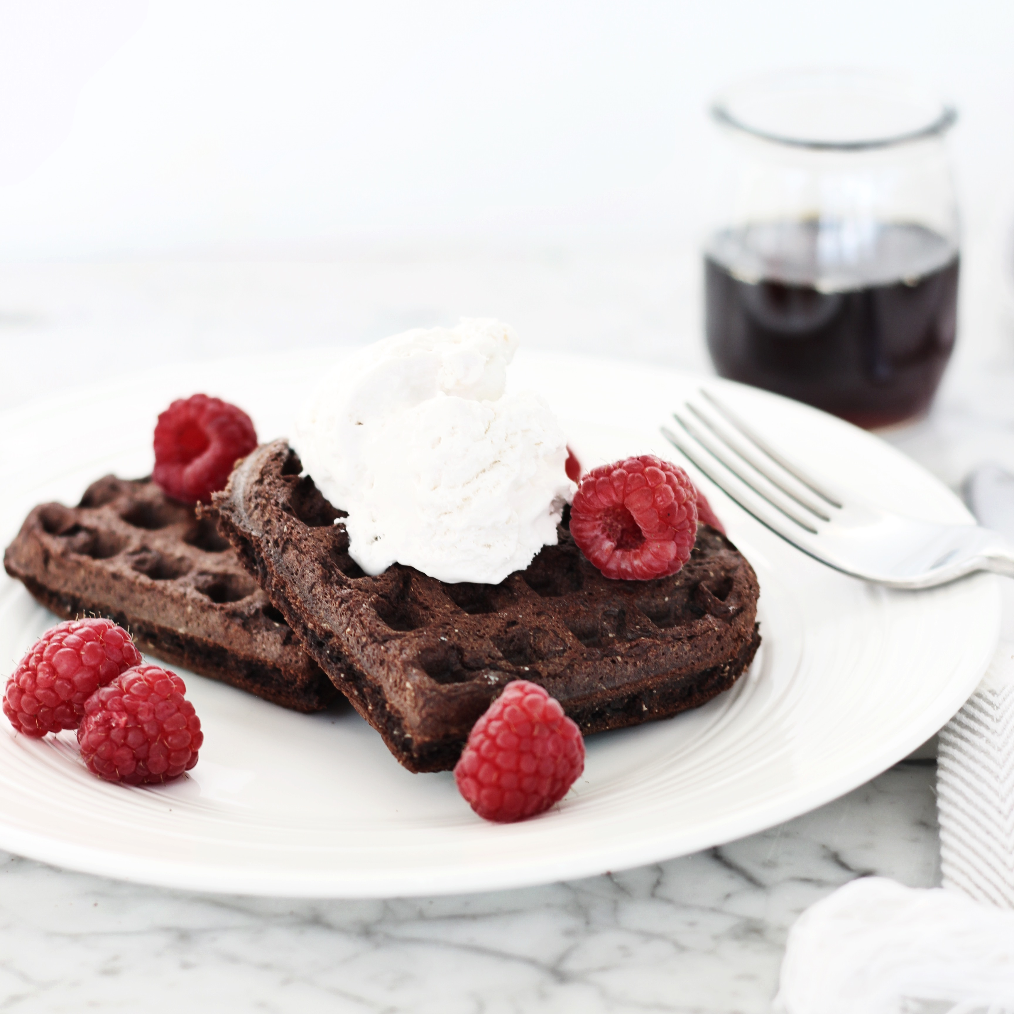 Chocolate Vegan Waffles on white plate with fresh raspberries
