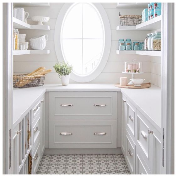 light grey pantry with oval window, open shelves and panelled walls