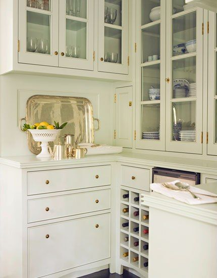 Warm white butler pantry with bar area and silver platters with brass hardware and glass cupboards