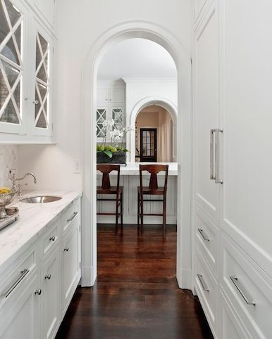 arched entry in white kitchen pantry