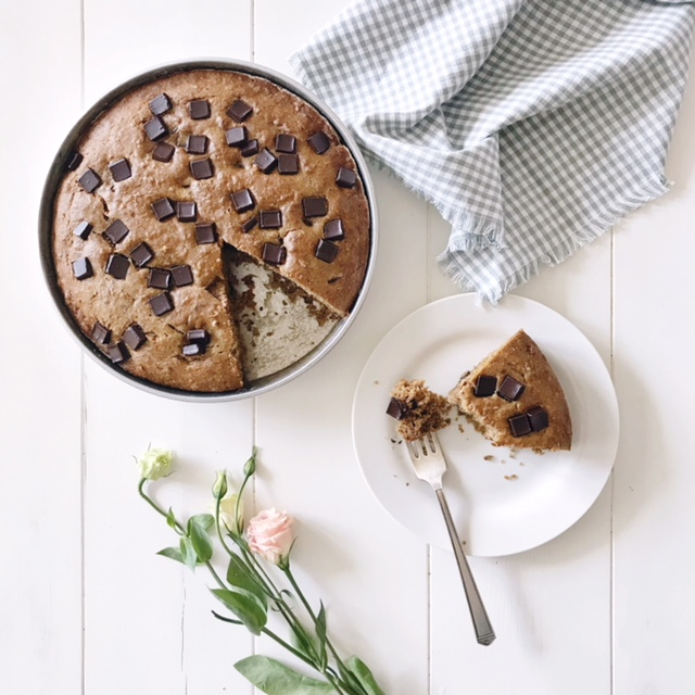 Chocolate Chunk Olive Oil Banana Cake with Lisianthus Flowers, a vintage fork and a Gingham napkin on a white farmhouse table