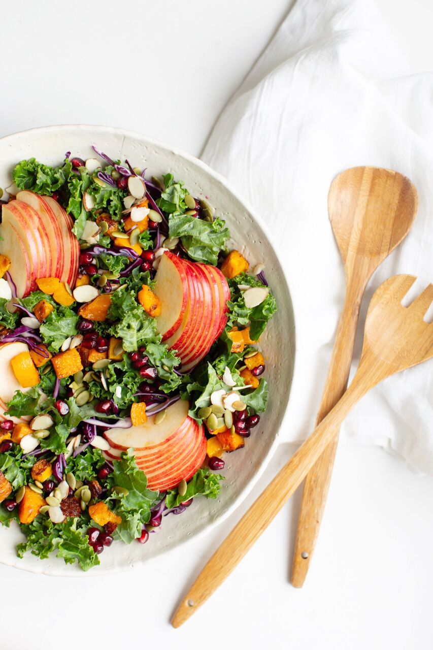Confetti Kale Salad filled with seasonal winter ingredients including pomegranates, crisp apples, shredded red cabbage, kale, roasted squash and almonds - completely gluten free and vegan.