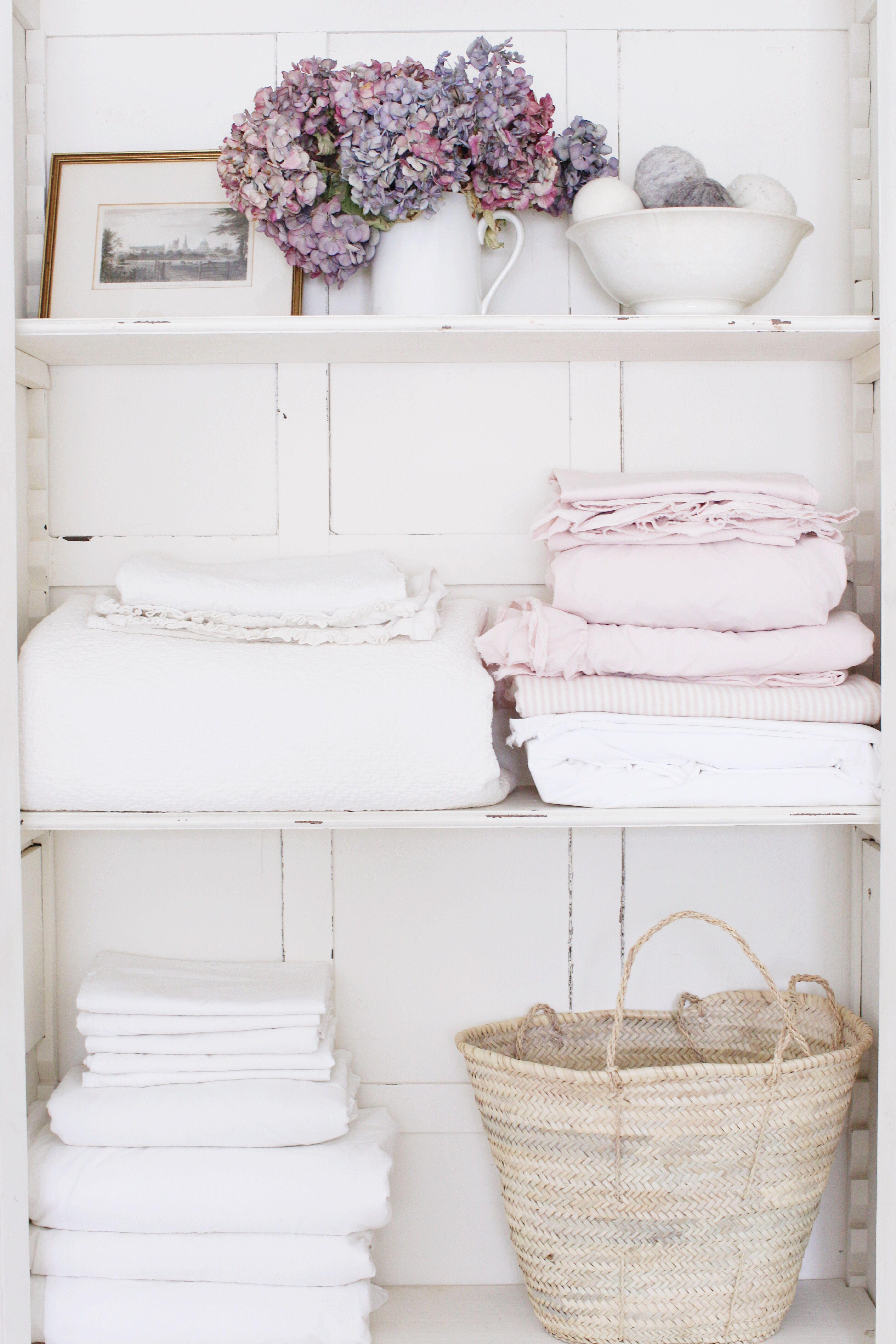 Antique cream linen cupboard with buffalo check wallpaper