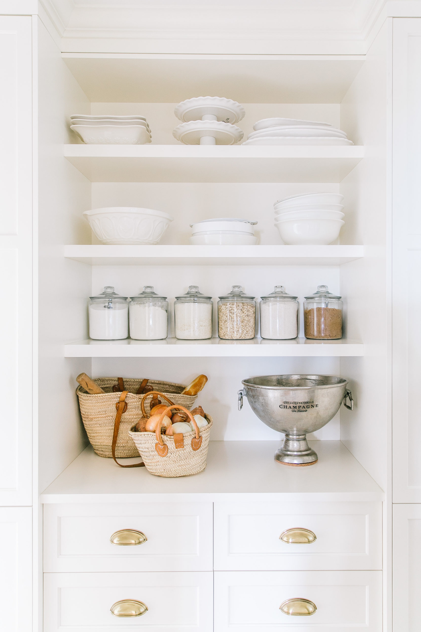 Our white butler's pantry reveal with an arched doorway, vintage chandelier lighting and open shelving with these white bowls, baskets and glass jars for storage!