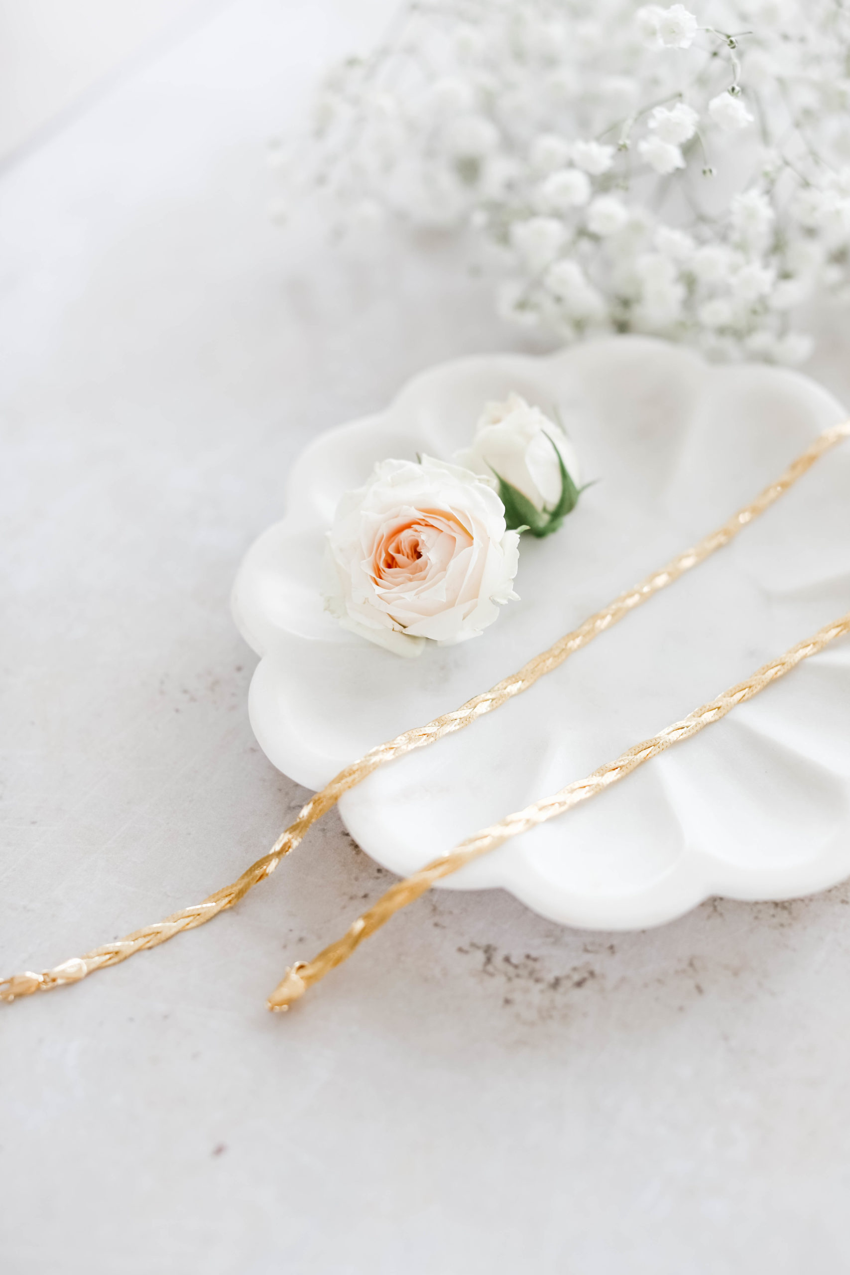 fraiche x so pretty gold herringbone bracelets in two lengths on a white tray with roses