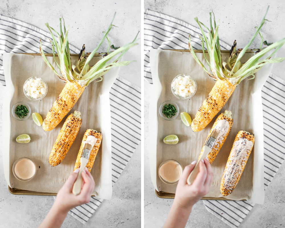 Hand brushing chipotle mayo onto corn on the cobs